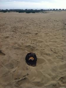 Sabres hat atop sand dune