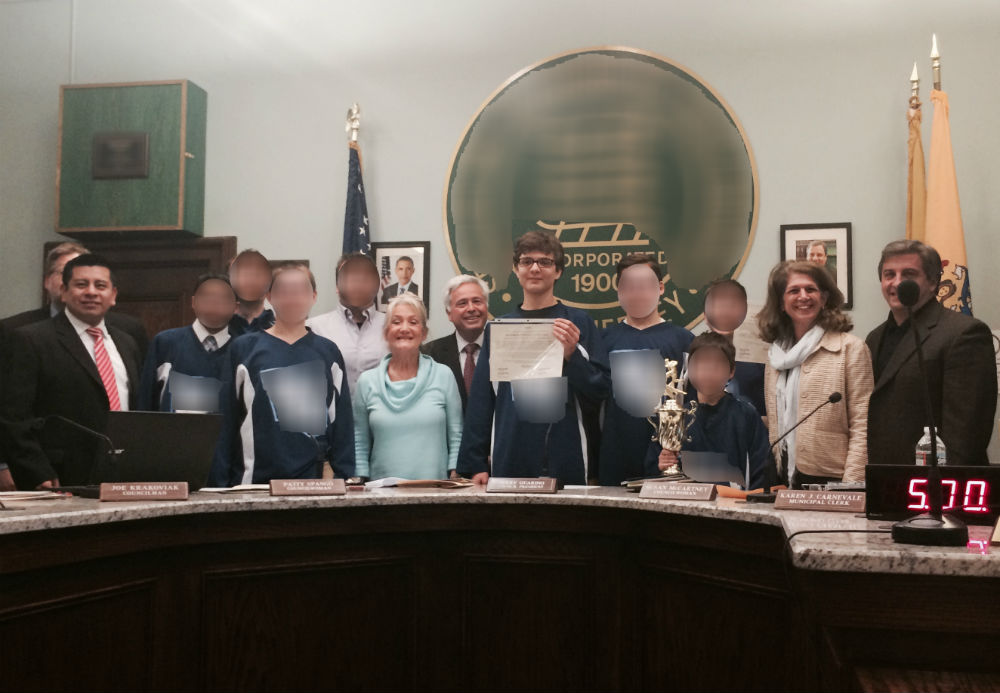 Ryan poses with the certificate, his teammates and coaches, and the mayor and town council members. (Note - I have blurred the faces of the other children and coaches.)